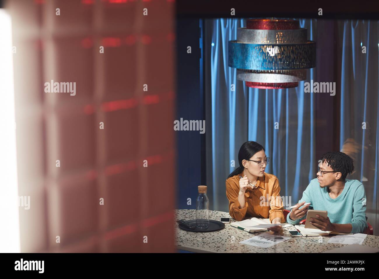 Wide angle portrait of two ethnic business people discussing project while working late in dark office, copy space Stock Photo