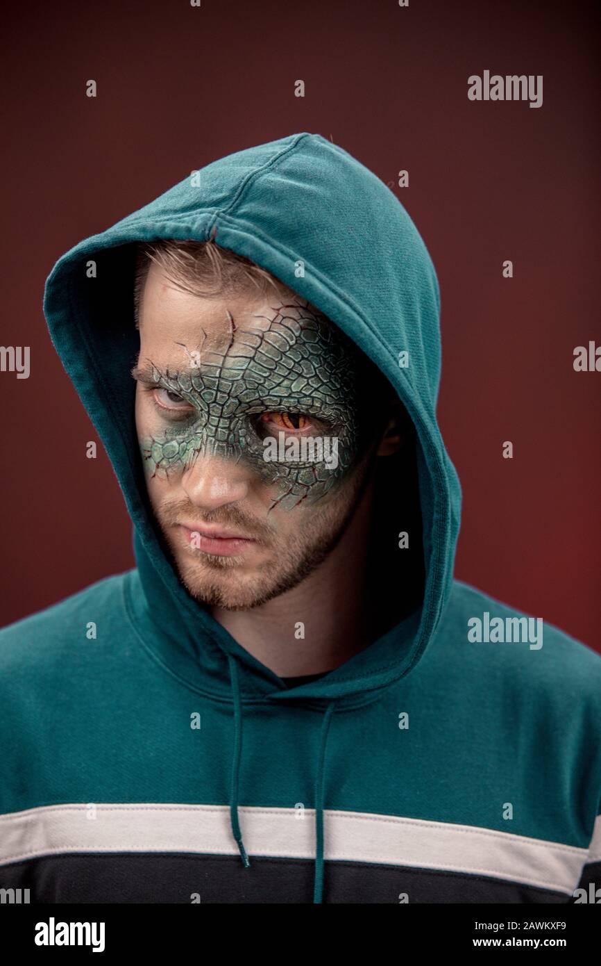 man with professional horror movie make-up green lizard on dark red background. lizard eye Stock Photo
