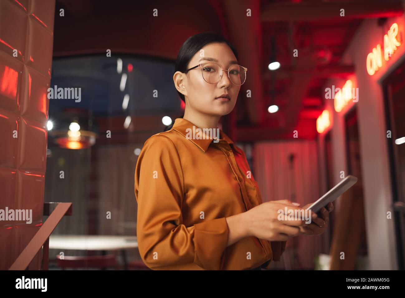 Waist up portrait of modern Asian businesswoman holding tablet and looking at camera while posing outdoors, copy space Stock Photo