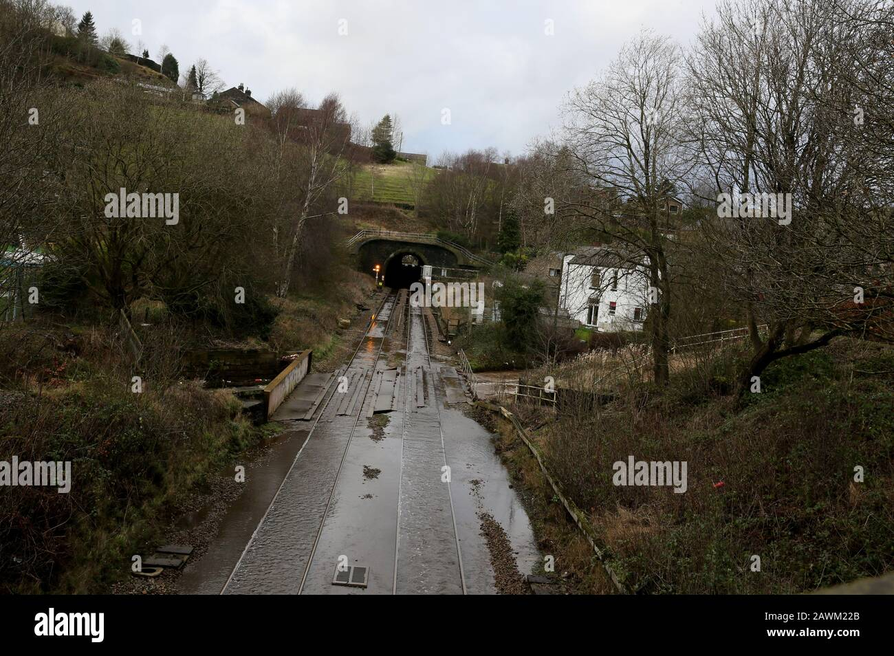 Marsden, UK. 9th February, 2020. Storm Ciara leaves a trail of damage in the Calder valley.  Rain has washed stones and  a railway sleeper onto the Rochdale to Todmorden Road.  A tree has fallen across the railway line.  A tractor is been used to take away flood water and empty it into the Rochdale canal.  Walsden, Calder Valley, West Yorkshire, UK. Credit: Barbara Cook/Alamy Live News Stock Photo
