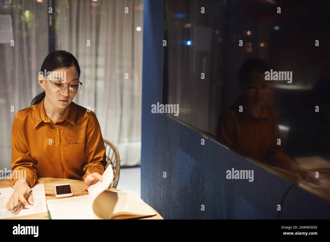 High angle portrait of contemporary Asian businesswoman working ad desk in dark office interior, copy space Stock Photo