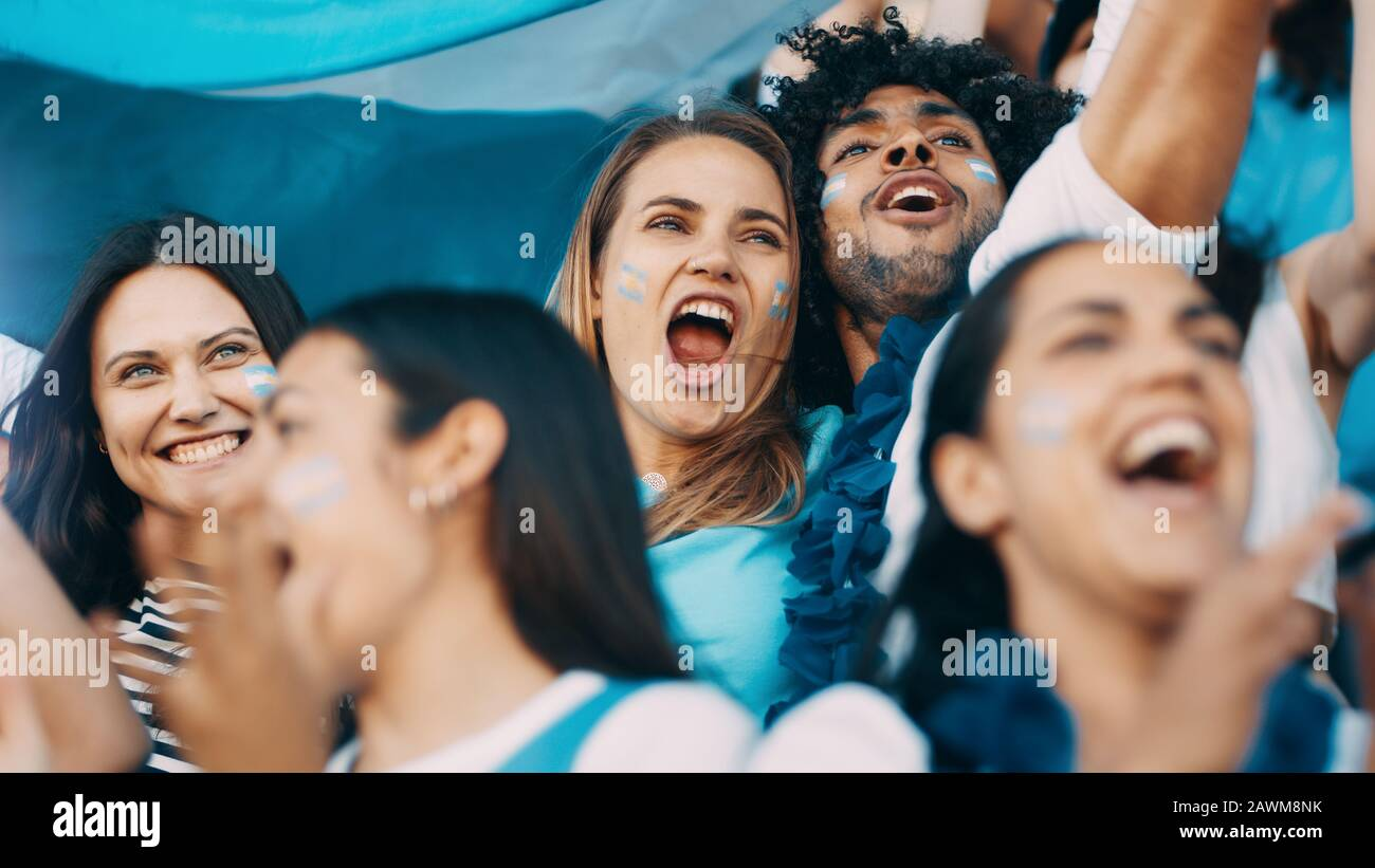 Excited sports fans at live game shouting and cheering for their team. People watching football match chanting to cheer argentinian national team. Stock Photo