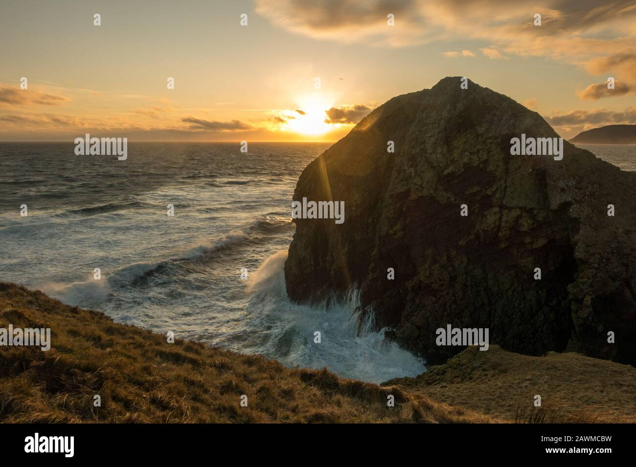 Roaring Cove at Dunaverty Castle and Dunaverty Rock with views behind of the Mull of Kintyre at sunset, Scotland Stock Photo