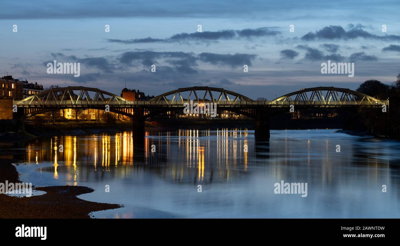 Barnes Railway Bridge in west London UK, a Grade II listed structure, photographed during blue hour on a cold, clear winter's evening. Stock Photo