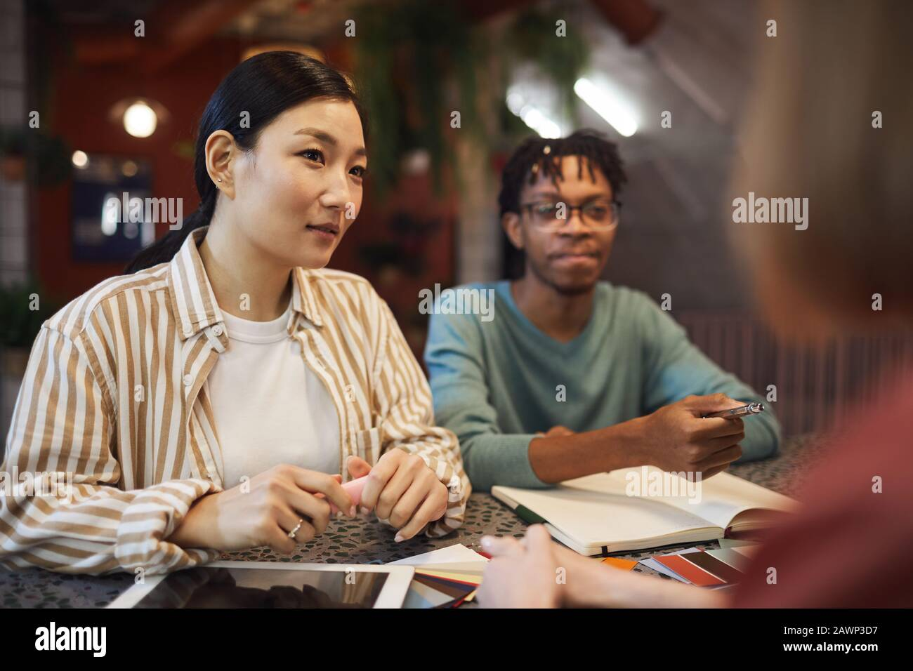 Multi-ethnic group of three business people working on project while sitting at table in cafe, copy space Stock Photo