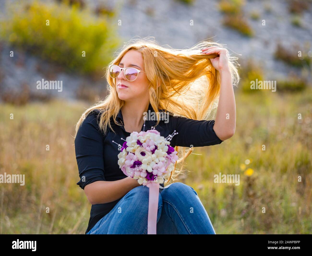 Teen girl hand holding flowery bouquet throwing up fixing hair looking away aside sunlight sunshine bright highlight Stock Photo