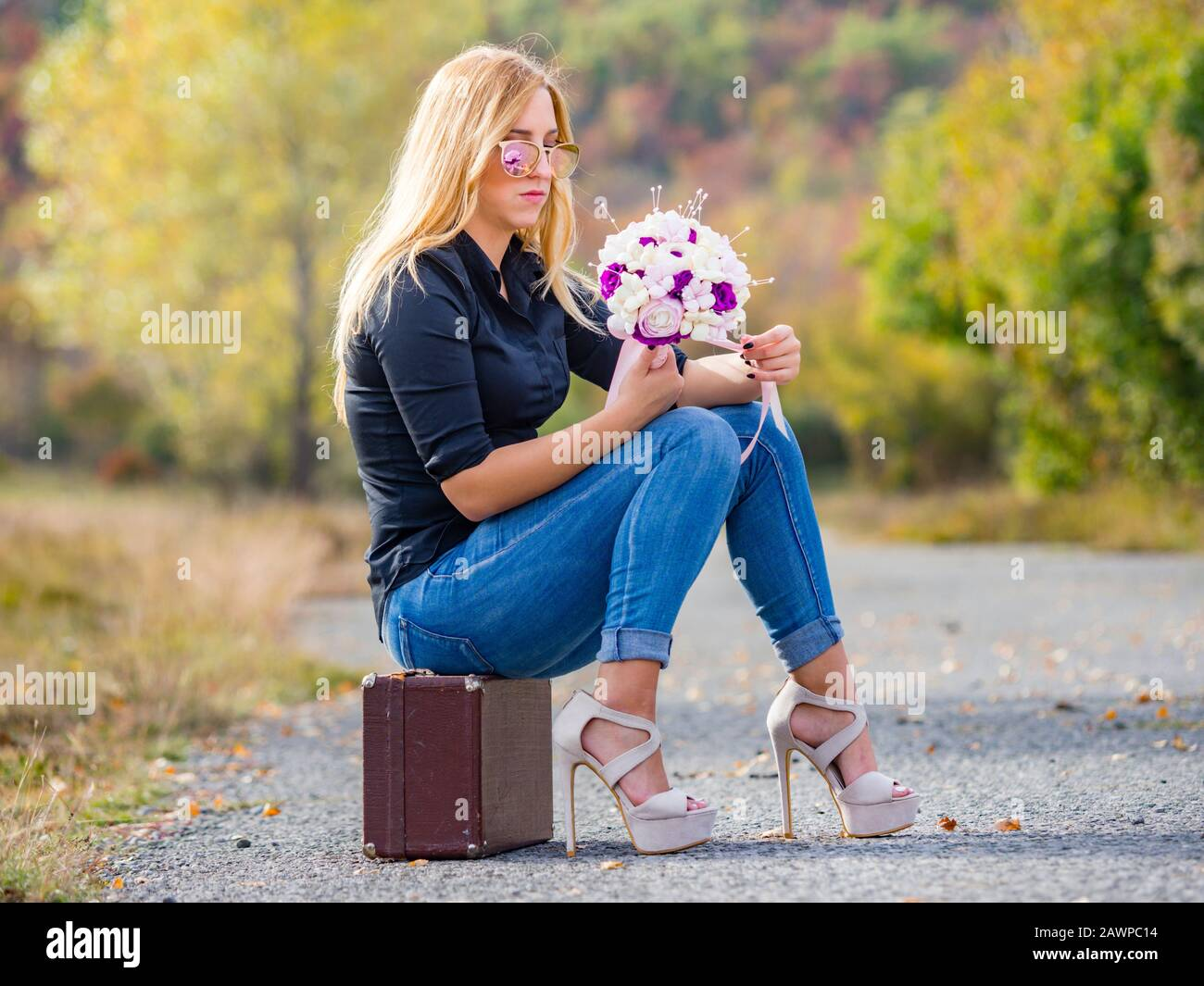 Teen girl sitting on boxy baggage case countryroad denim pants legs heels hand holding flowery bouquet indifferent Stock Photo
