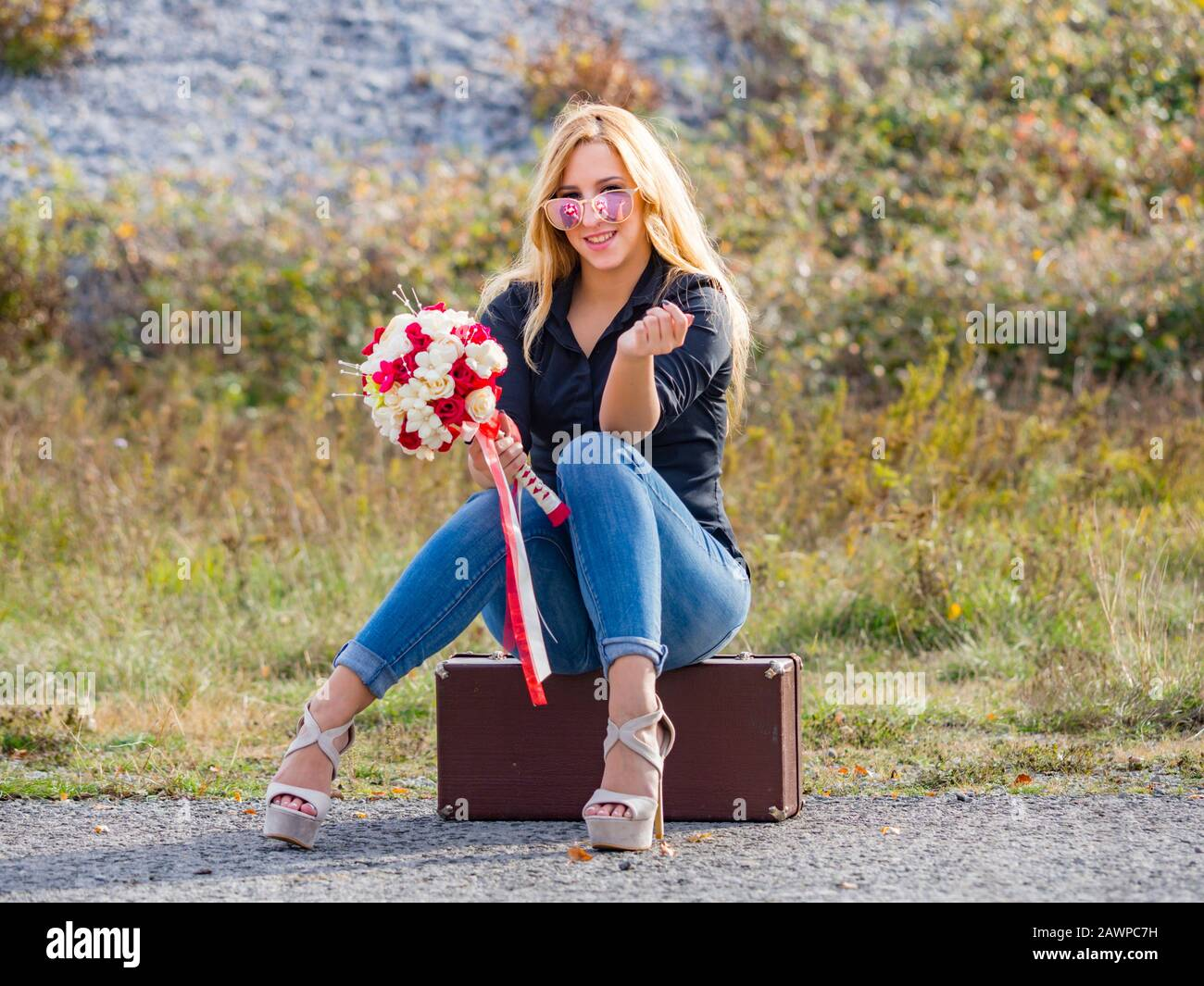 Teen girl sitting on boxy baggage case denim pants legs heels hand holding flowery bouquet looking at camera slight smile Stock Photo