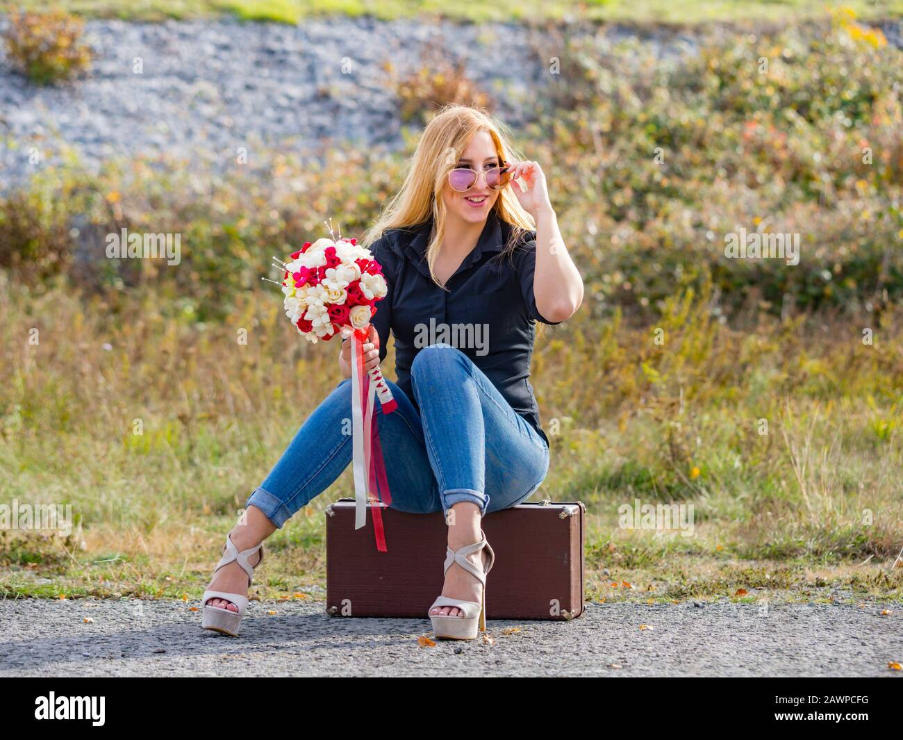Teen girl sitting on boxy baggage case denim pants legs heels hand holding flowery bouquet smiling positive feeling expected expecting expect looking Stock Photo