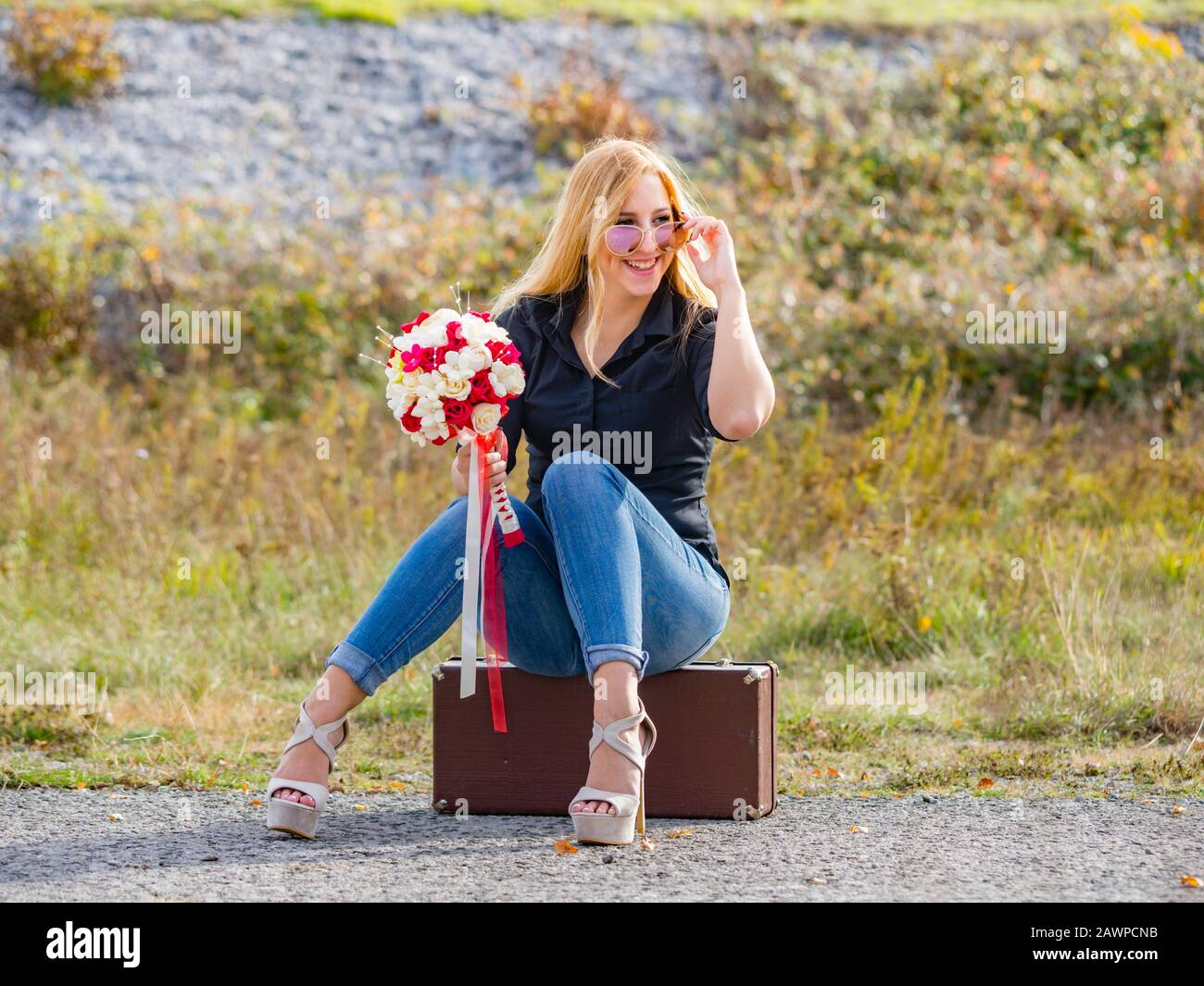 Teen girl sitting on boxy baggage case denim pants legs heels looking away aside smiling positive feeling expected expecting expect Stock Photo