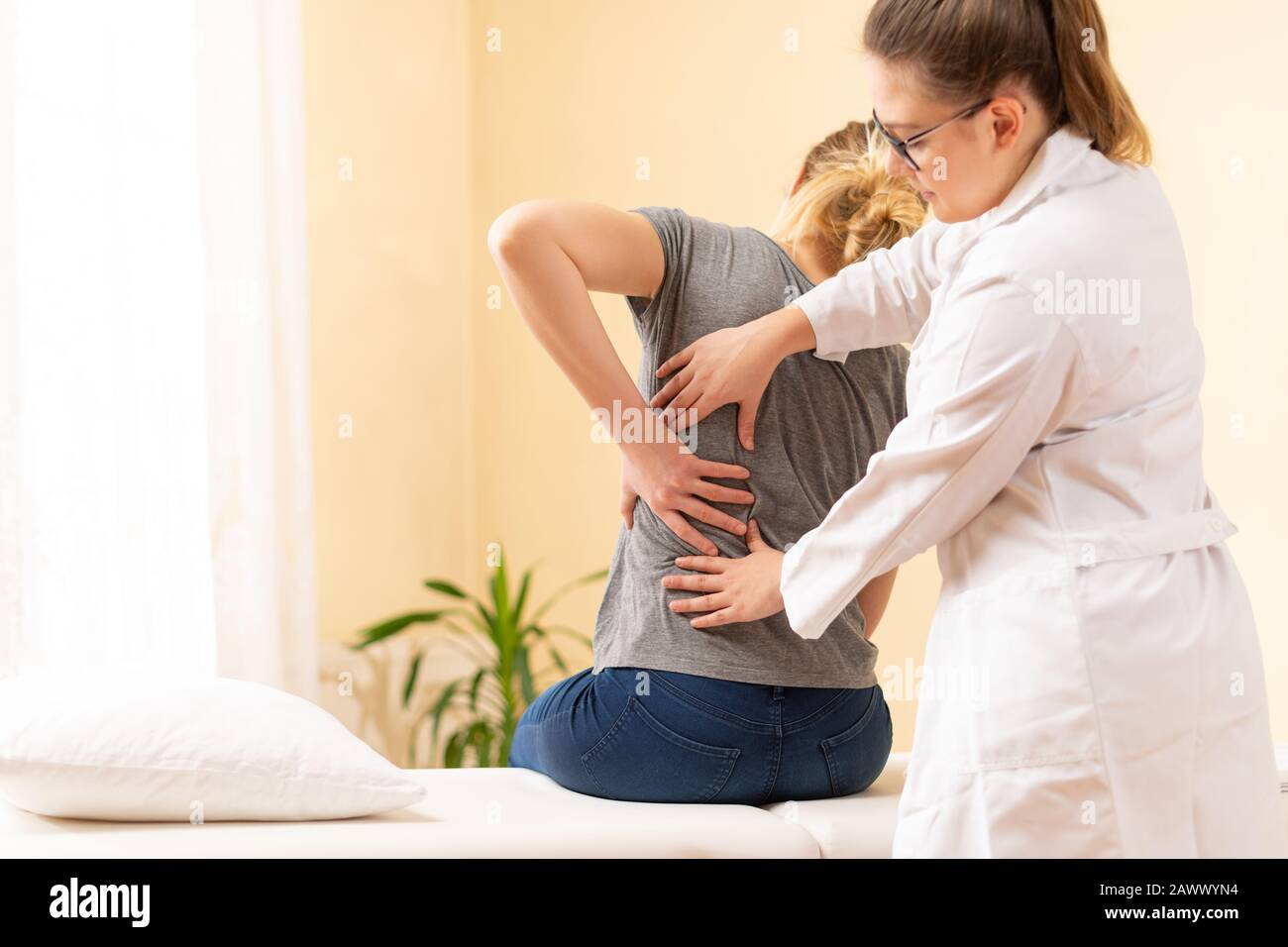 Female physiotherapist or a chiropractor examining patients back. Physiotherapy, rehabilitation concept. Stock Photo