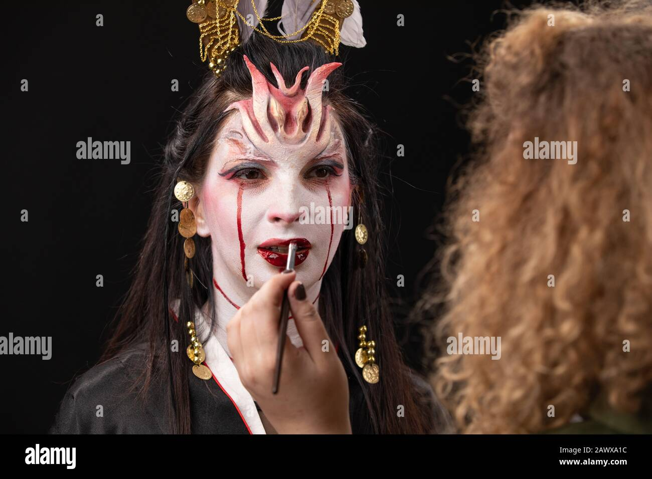 Witchcraft Asian woman in scary Witch ghost story look, mouth blood wound black long hair, studio lighting dark red background. makeup artist doing Stock Photo