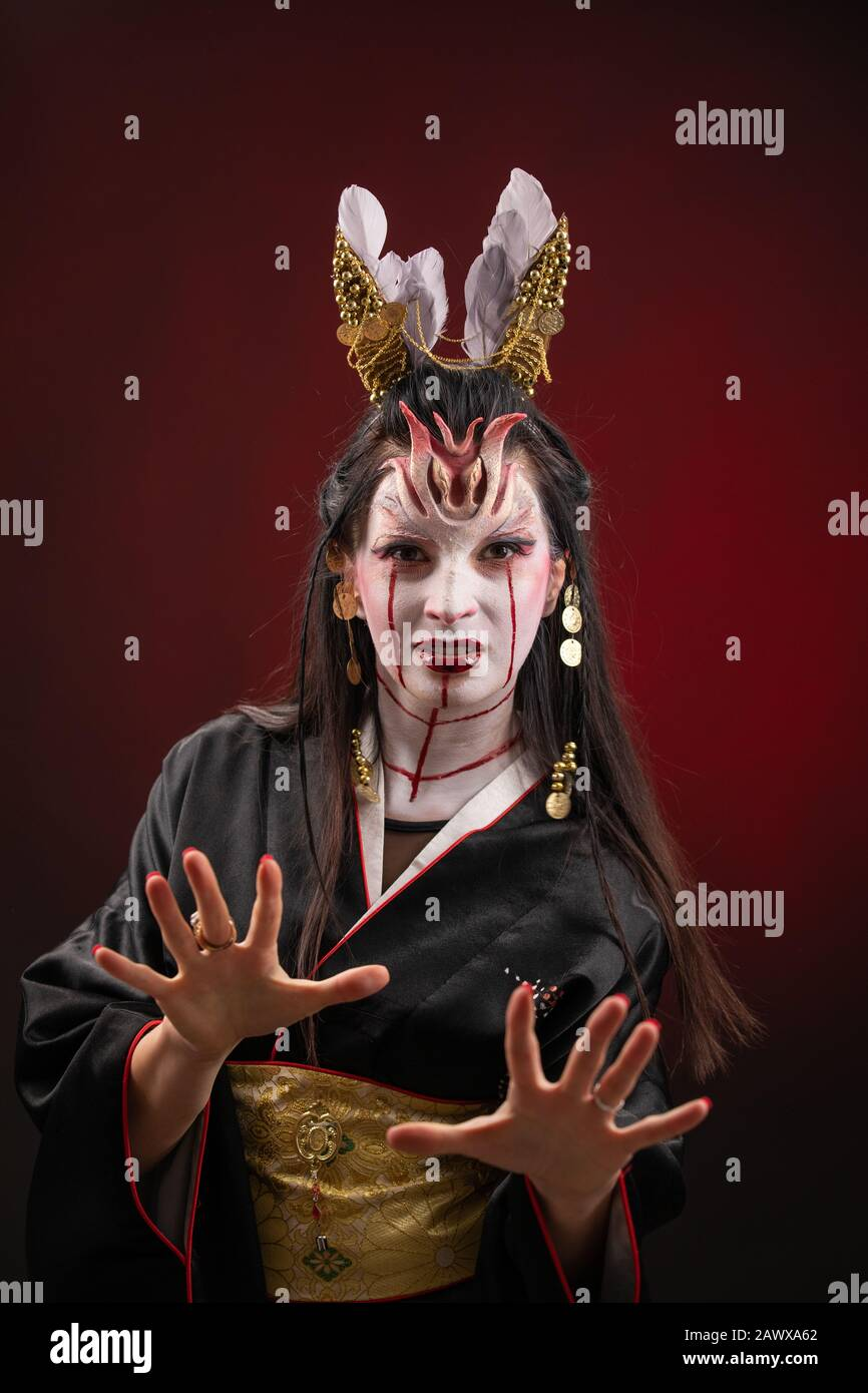 Witchcraft Asian woman in scary Witch ghost story look, mouth blood wound black long hair, studio lighting dark red background. Make up for halloween Stock Photo