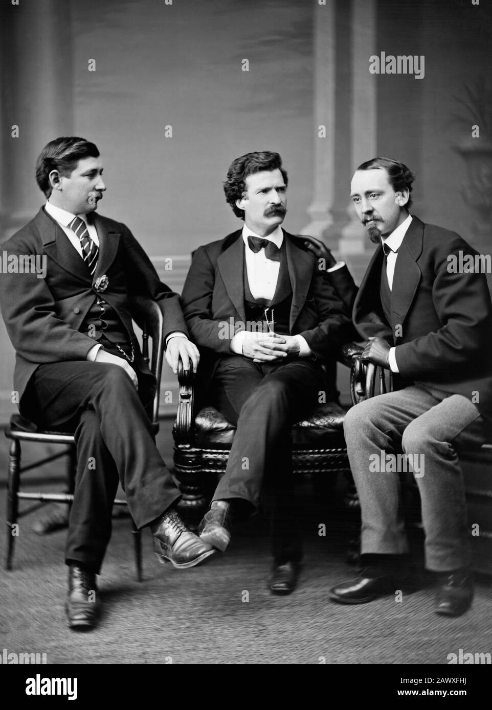 Vintage photo of American writer and humourist Samuel Langhorne Clemens (1835 – 1910), better known by his pen name of Mark Twain. Clemens is seated in the centre with, on the left of the picture, journalist and novelist George Alfred Townsend (1841 – 1914) and, on the right, David Gray (1836 - 1888) of the Buffalo Courier. Photo by Brady - Handy taken in Washington DC in 1871. Stock Photo