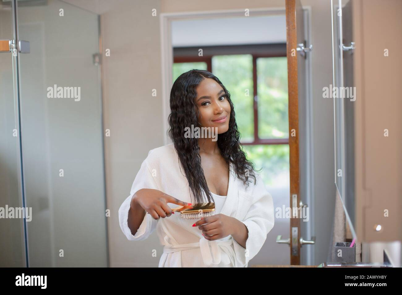 Portrait beautiful smiling young woman brushing hair in bathroom Stock Photo