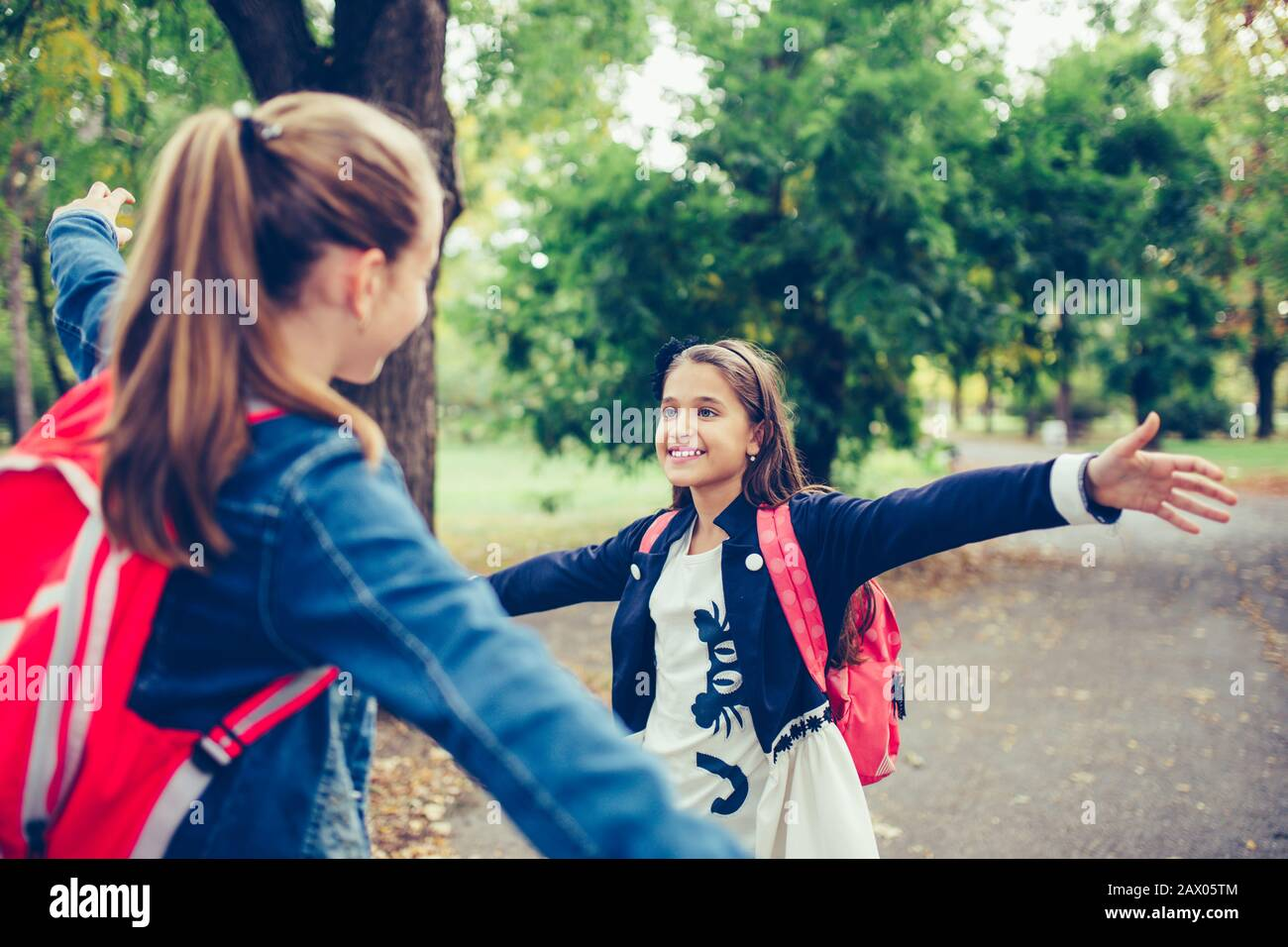 Two school friends hugging, meet in the park. Walking into each other with open arms and smiling. The concept of school, study, education, friendship, Stock Photo
