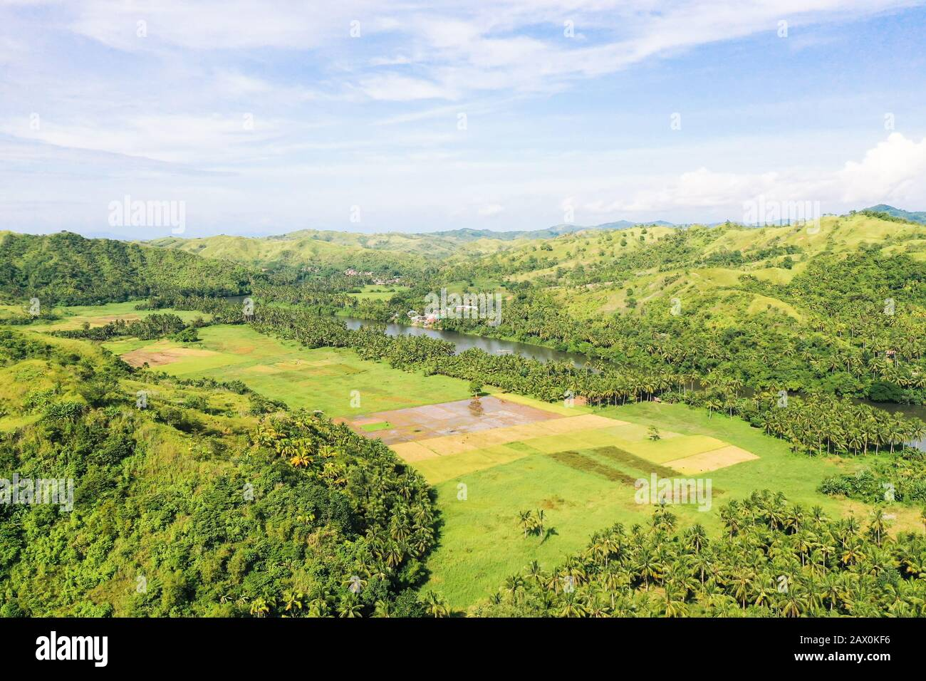 River and green hills. Beautiful natural scenery of river in southeast Asia. Countryside on a large tropical island. Small village on the green hills by the river. The nature of the Philippines. Stock Photo