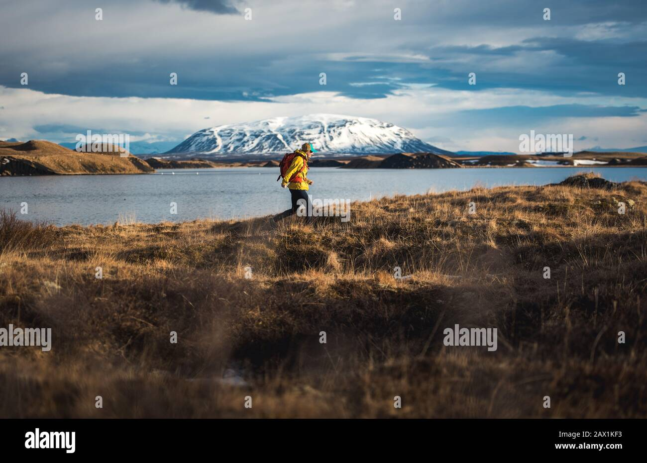 Woman walking through field next to lake with mountains in distance Stock Photo