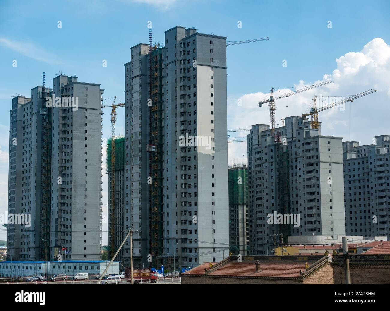 High rise apartment tower blocks under construction towering above traditional buildings,  Jining, China, Asia Stock Photo