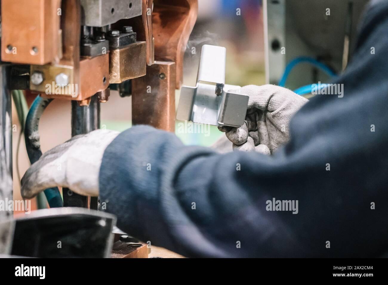 Spot welding machine Industrial automotive part in factory. Operator working in industry . Stock Photo