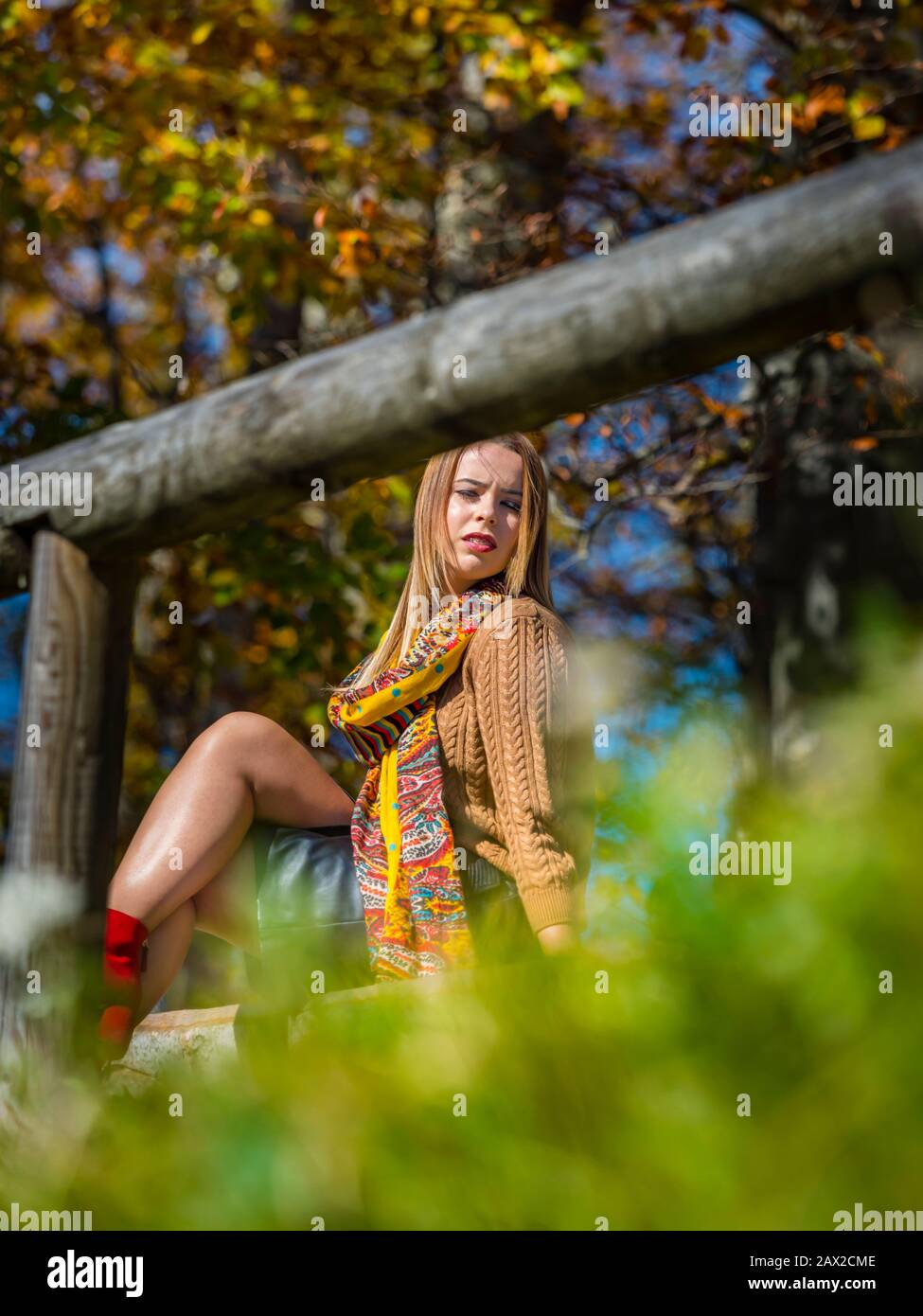 Autumn in forest teen girl isolated bellow wooden fence blurry background vegetation exposed leg legs knee knees serious looking away aside Stock Photo