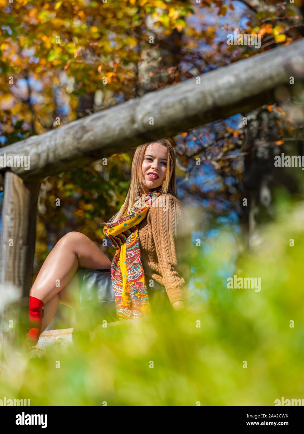 Autumn in forest teen girl isolated bellow wooden fence blurry background vegetation exposed leg legs knee knees looking aside smiling smile away Stock Photo