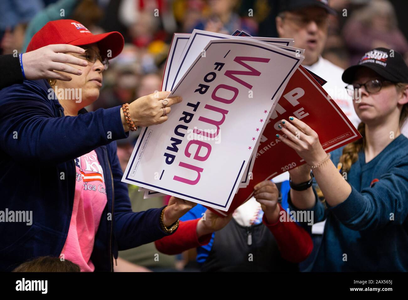 Manchester, United States. 10th Feb, 2020. Fans of United States President Donald Trump hand out signs before the start of a 2020 re-election campaign rally held by President Trump at the SNHU Arena in Manchester, New Hampshire on Monday, February 10, 2020. New Hampshire holds the first presidential primary in the nation on Tuesday. Photo by Matthew Healey/UPI Credit: UPI/Alamy Live News Stock Photo