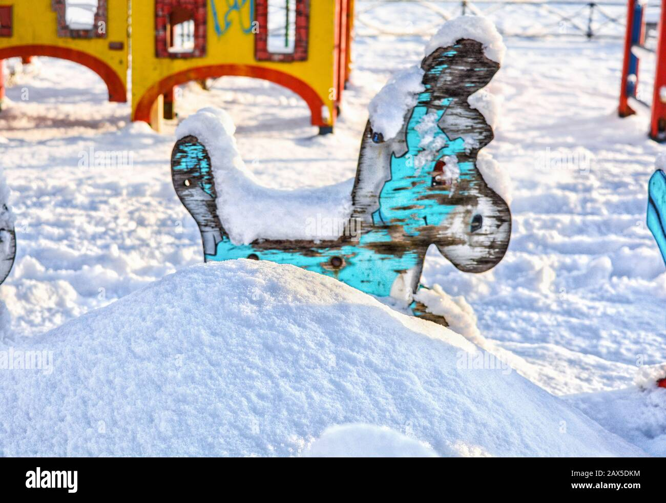 Old children carousel with blue donkey on snow-covered children playground is covered with white fluffy snow. Snowdrift with wooden donkey Stock Photo