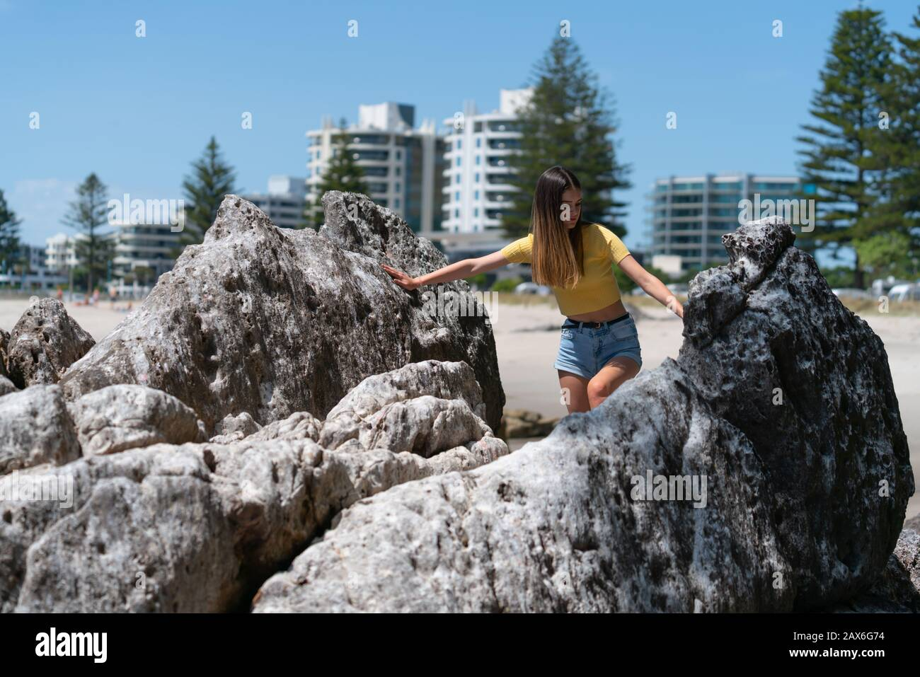 Teenage girl in yellow top and denim short pants climbs over and between rocks on Mount Maunganui main beach with Norfolk Pines and apartment building Stock Photo