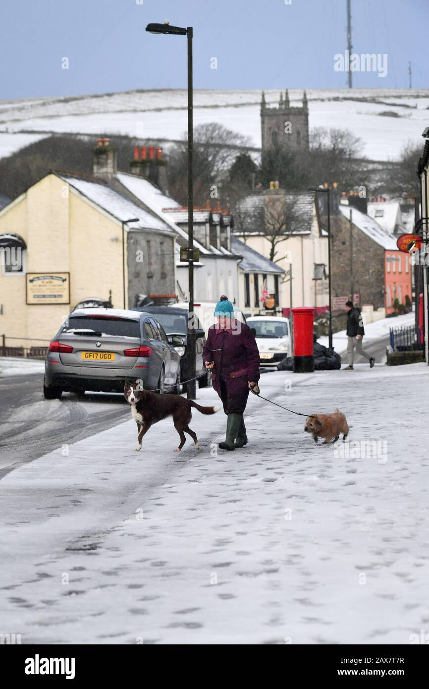 A dog walker walks along snow covered footpaths in Princetown on the top of Dartmoor, Devon, where snow has fallen on high ground. Stock Photo