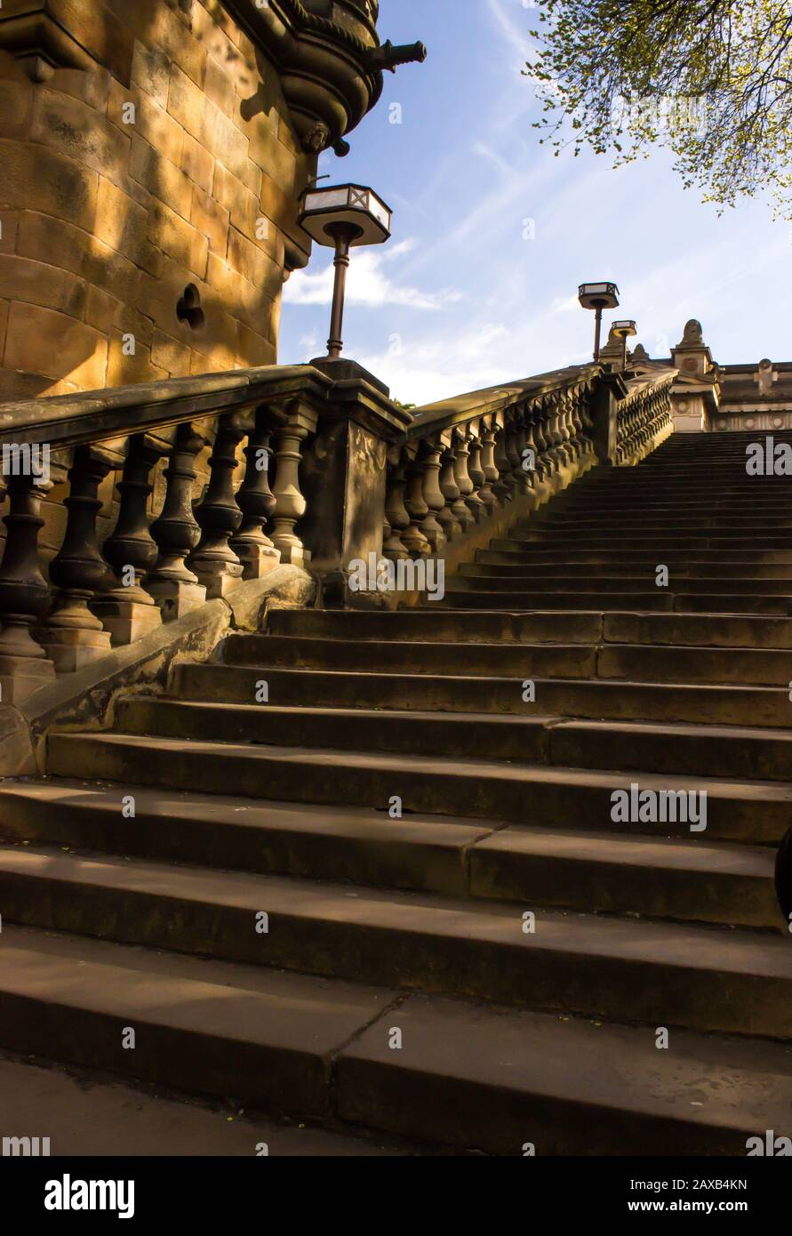 Staircase leading out of the filled in Loch of Princess Street Gardens, Edinburgh, covered in the dappled light and shadow Stock Photo