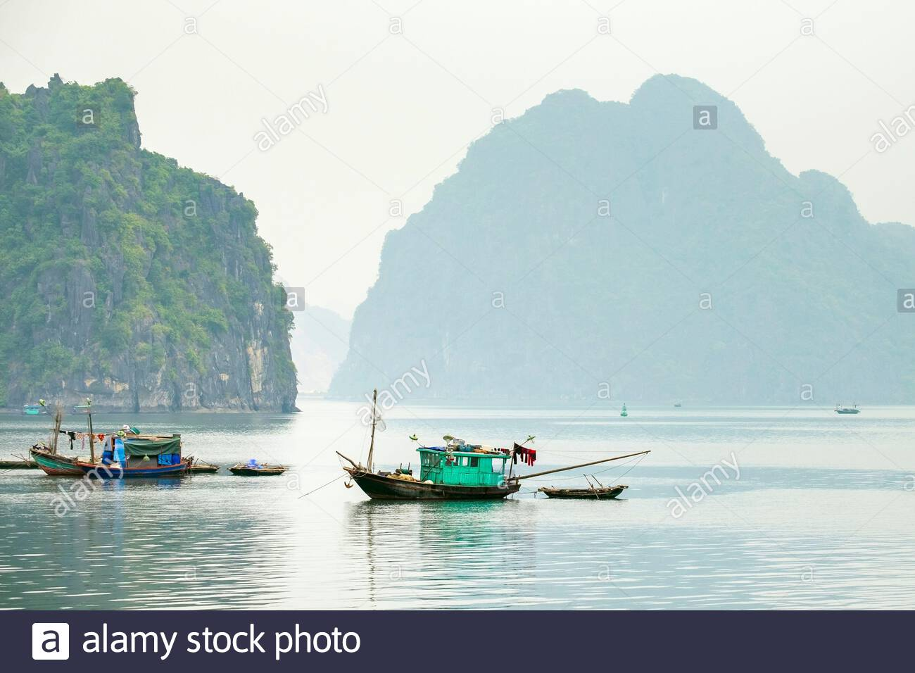 Boats in Ha Long bay on a foggy morning, Quang Ninh Province, Vietnam Stock Photo