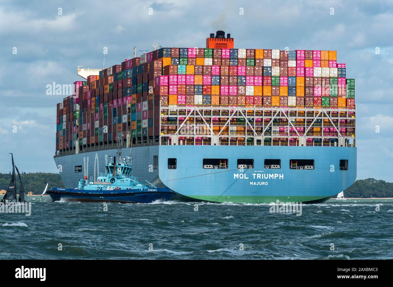a large container cargo ship entering the port of southampton docks with a tug helping to steer the large massive seagoing vessel in the solent. Stock Photo