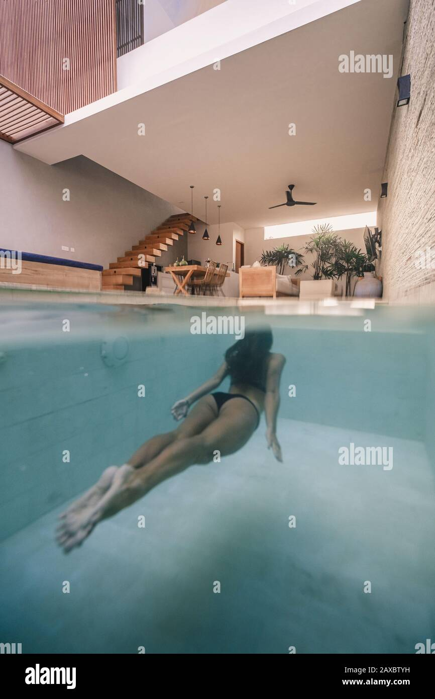 A vertical shot of a woman swimming in an in-house pool Stock Photo - Alamy