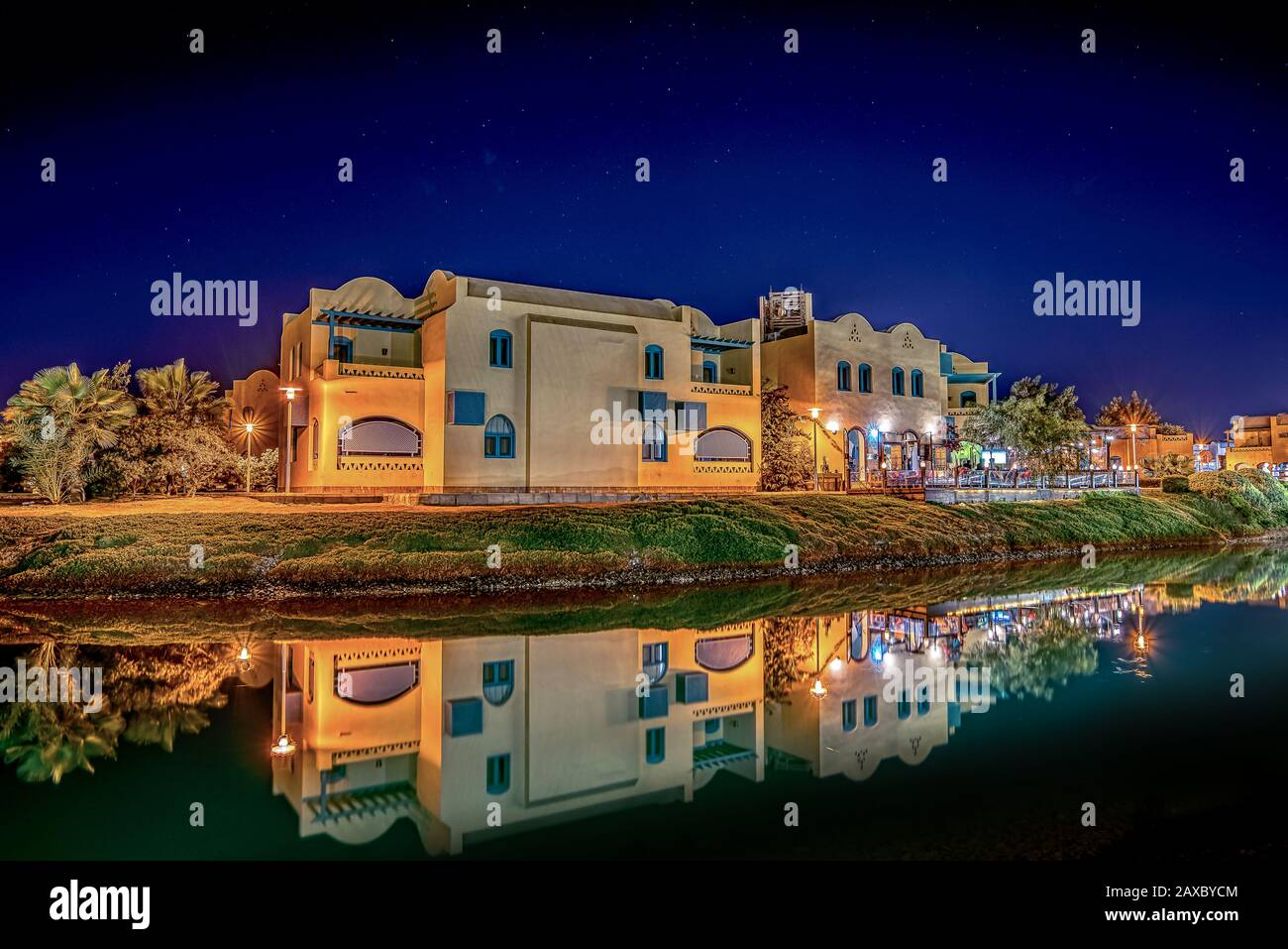 Egyptian houses at the side of the lagoon, reflecting in the water at night, el Gouna, Egypt, January 16, 2020 Stock Photo