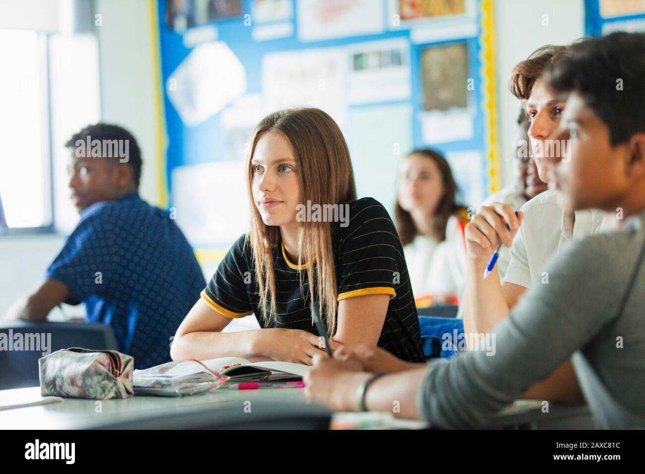 Close up focused, attentive high school girl student listening in classroom Stock Photo