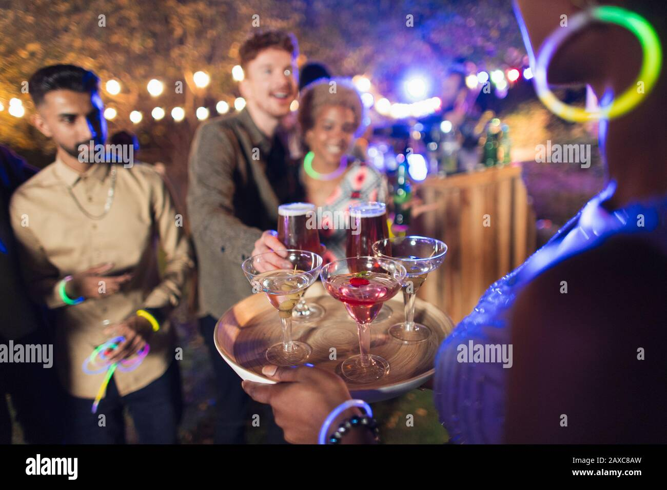 Woman serving cocktails to friends at garden party Stock Photo