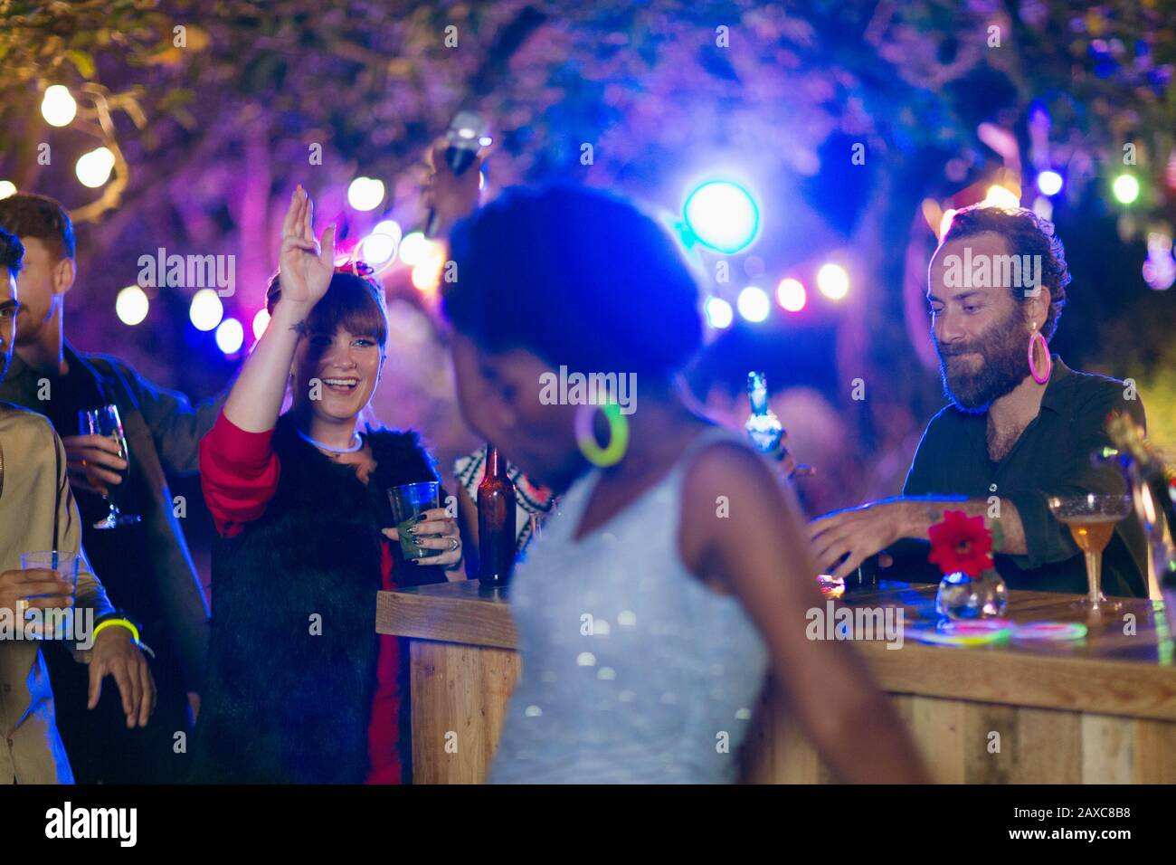 Friends dancing and drinking at garden party Stock Photo