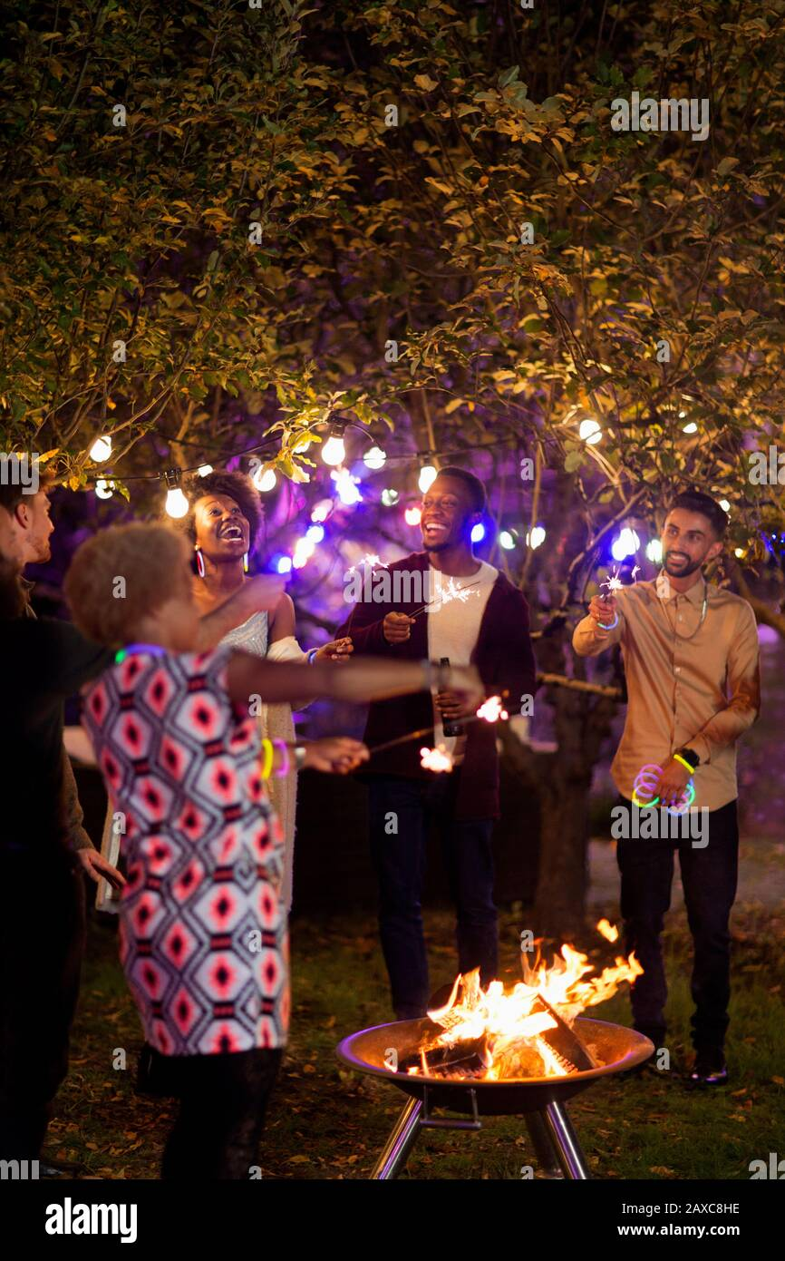 Happy friends with sparklers around fire pit at garden party Stock Photo