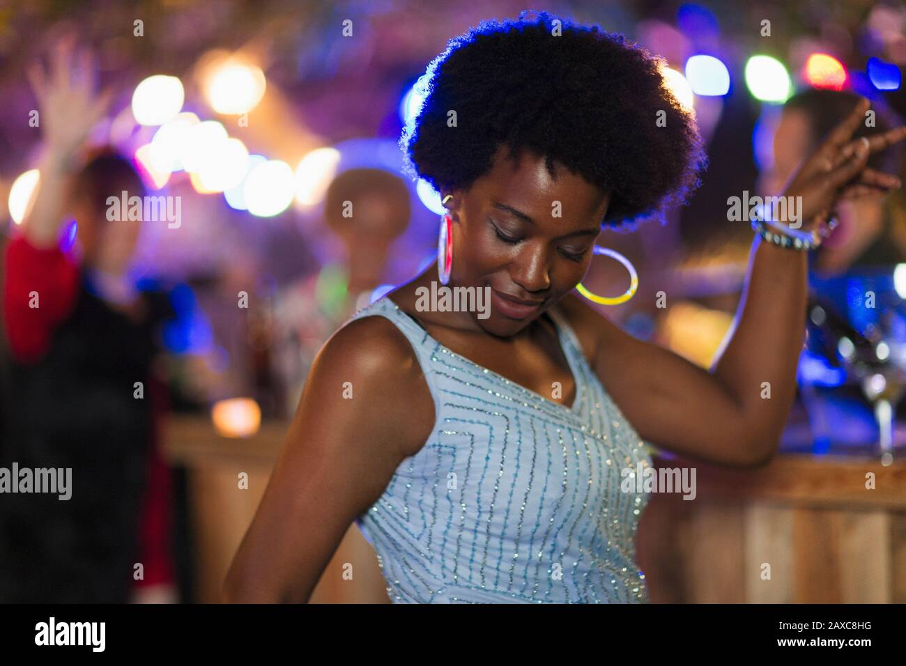 Carefree woman with neon earrings dancing at party Stock Photo