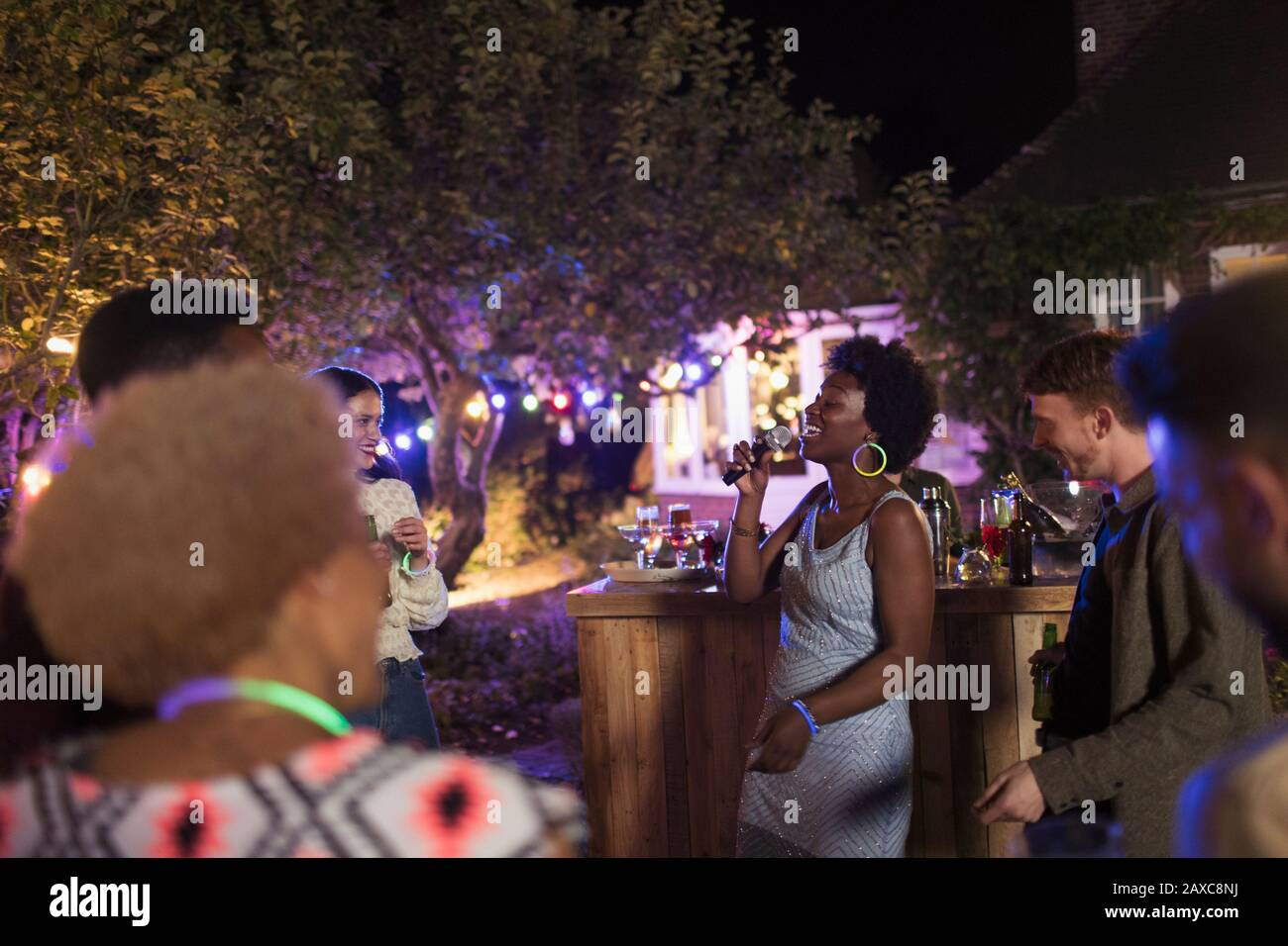 Young woman with microphone singing at garden party Stock Photo