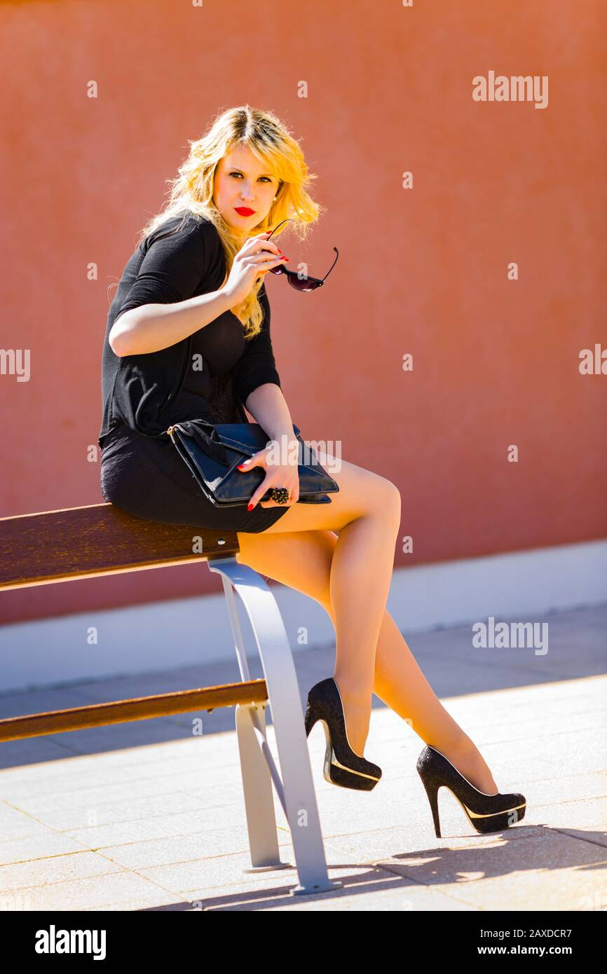 Young woman blonde blond fair-haired fairhair fairhaired legs in heels sitting inclined on wooden bench hand holding hold glasses looking at camera Stock Photo