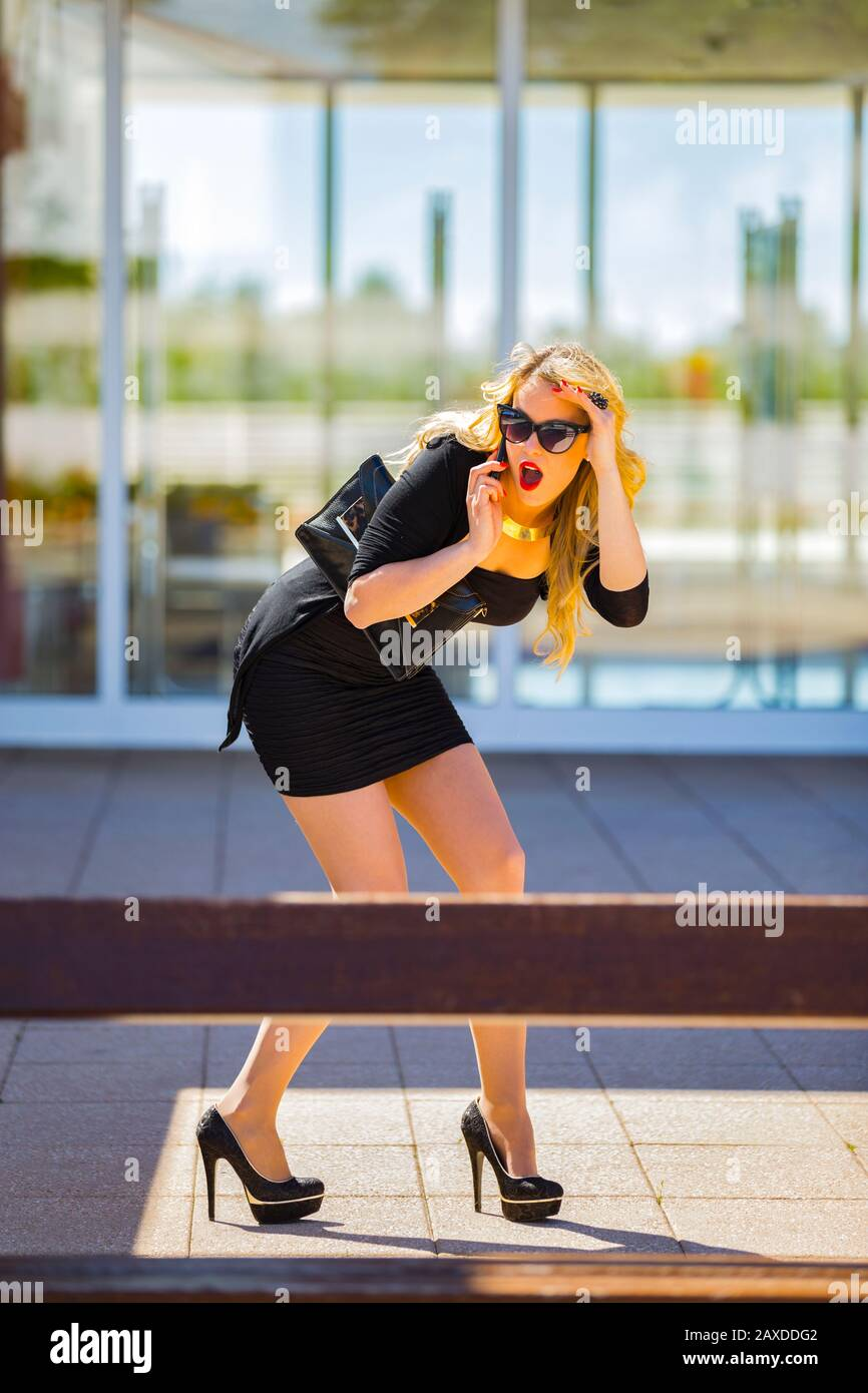Young woman blonde blond fair-haired fairhair fairhaired legs in heels is looking away surprised surprise excited excitement suddenly called negative Stock Photo