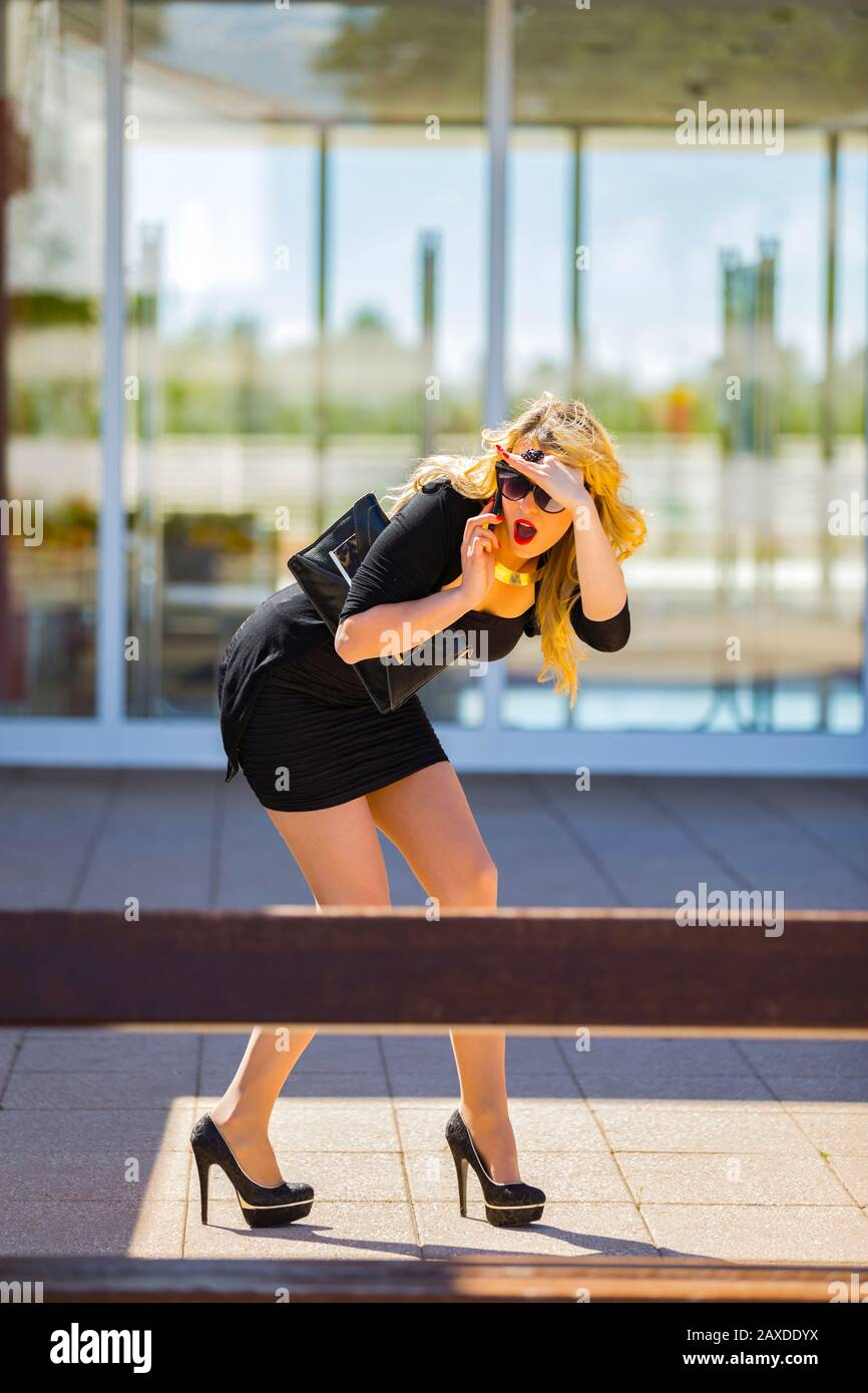 Young woman blonde blond fair-haired fairhair fairhaired legs in heels surprised surprise excited excitement suddenly called negative feeling Stock Photo