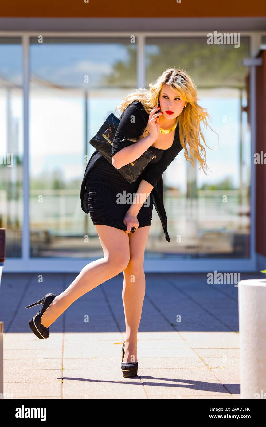 Young woman blonde blond fair-haired fairhair fairhaired legs in heels balancing balance on one leg talking talk using cellphone hand holding on ear Stock Photo