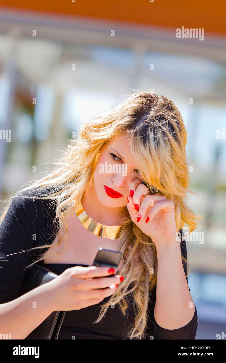 Young woman blonde blond fair-haired fairhair fairhaired is crying after  receiving bad news cry negative hand brushing tears from eye eyes Stock Photo