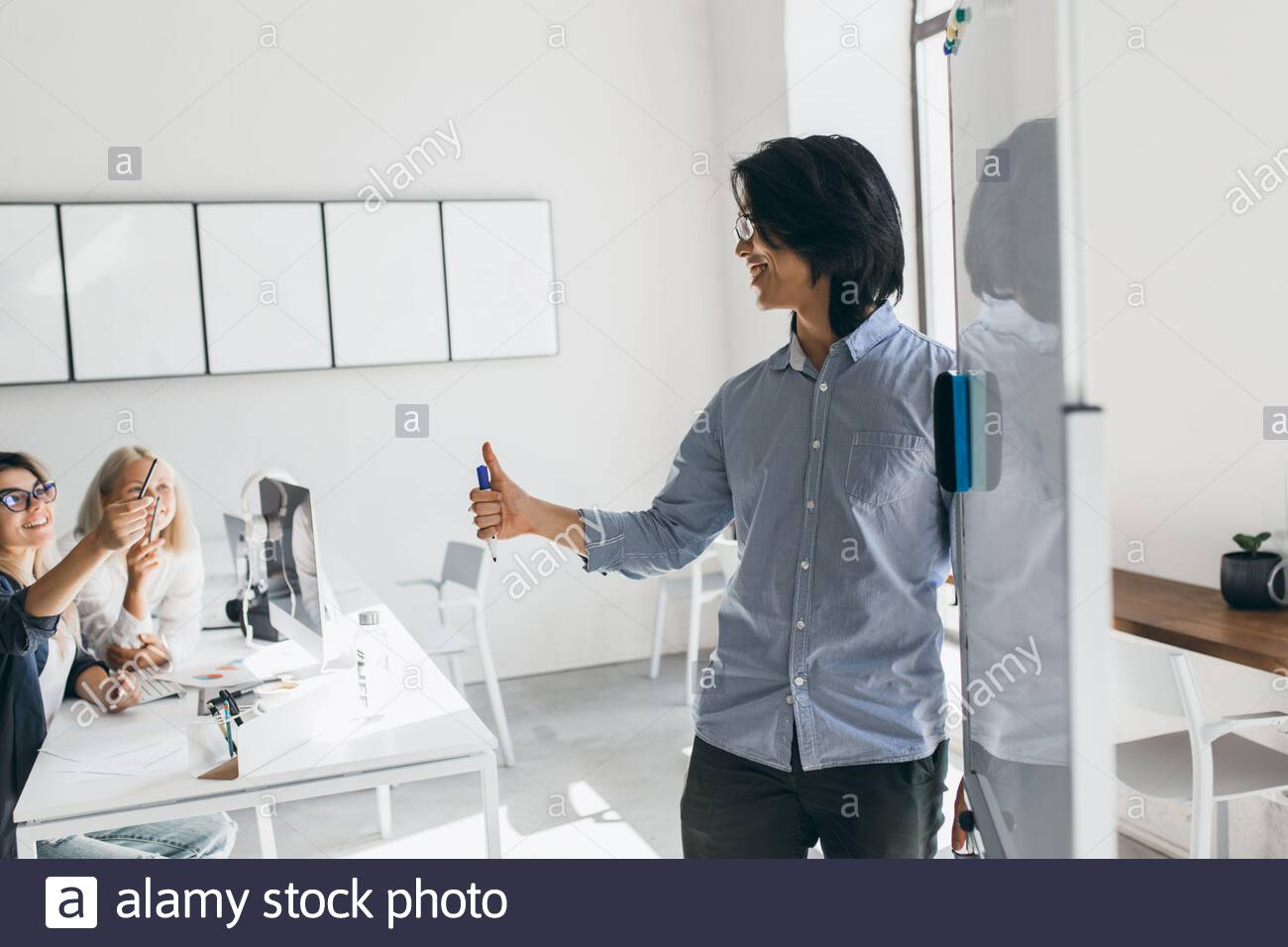 Asian developer standing near flipchart and looking at blonde girl in glasses. Indoor portrait of brunette businessman writing graph at white board and listening colleagues. Stock Photo