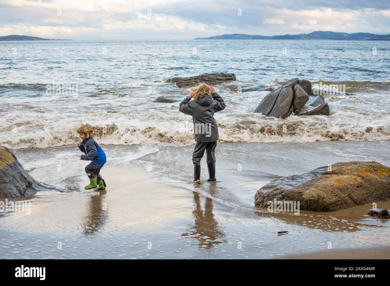 Children in gumboots playing and having fun by the seaside in Tasmania Stock Photo