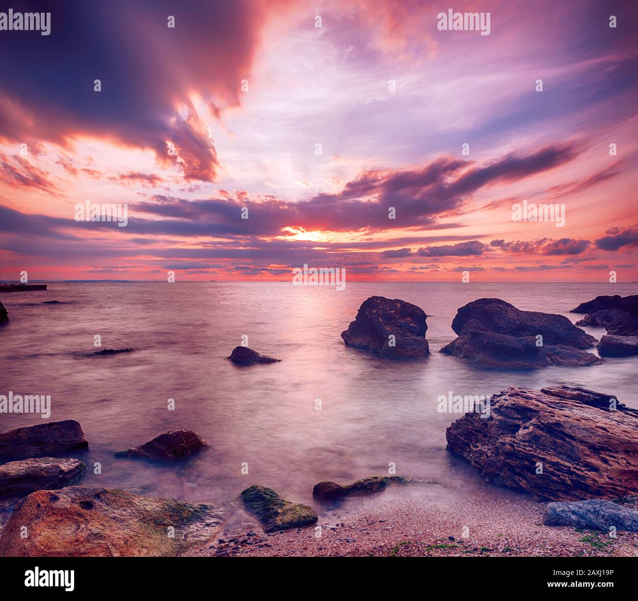 Beautiful colorful sunrise at the sea with dramatic clouds and boulders. Beauty world natural outdoors travel background Stock Photo