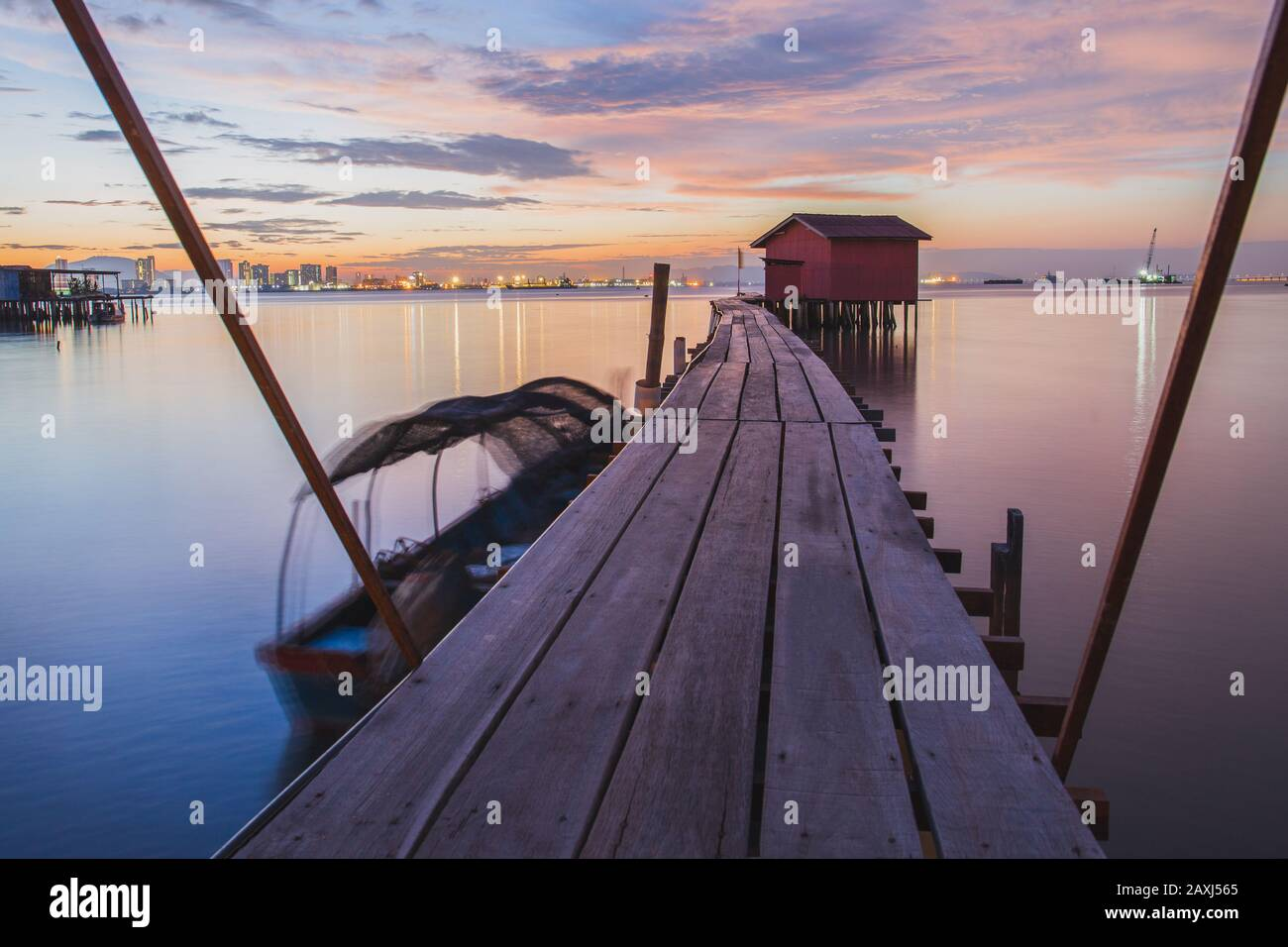 Wooden bridge with hut at sunrise in Chew jetty Georgetown Penang. Stock Photo